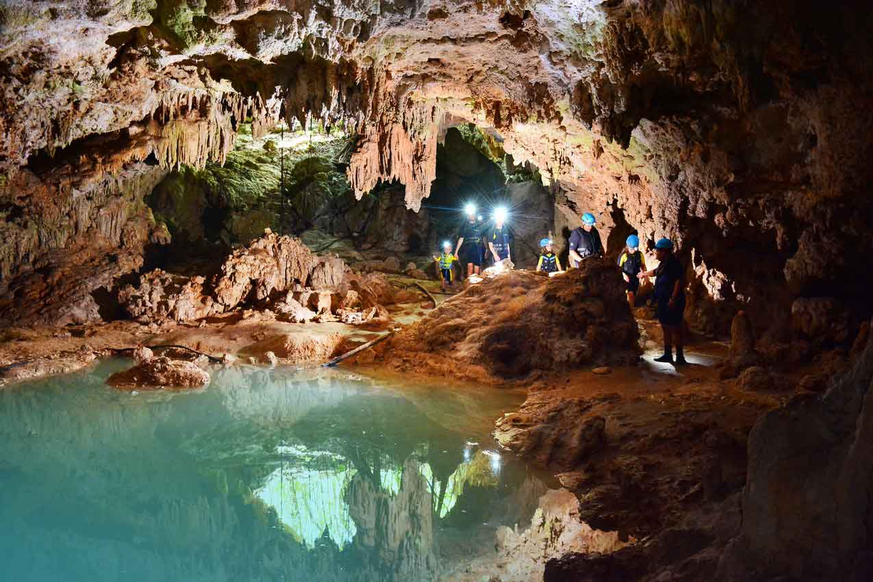 five-guests-and-guide-walking-in-cave-during-rio-secreto-riviera-maya-tour