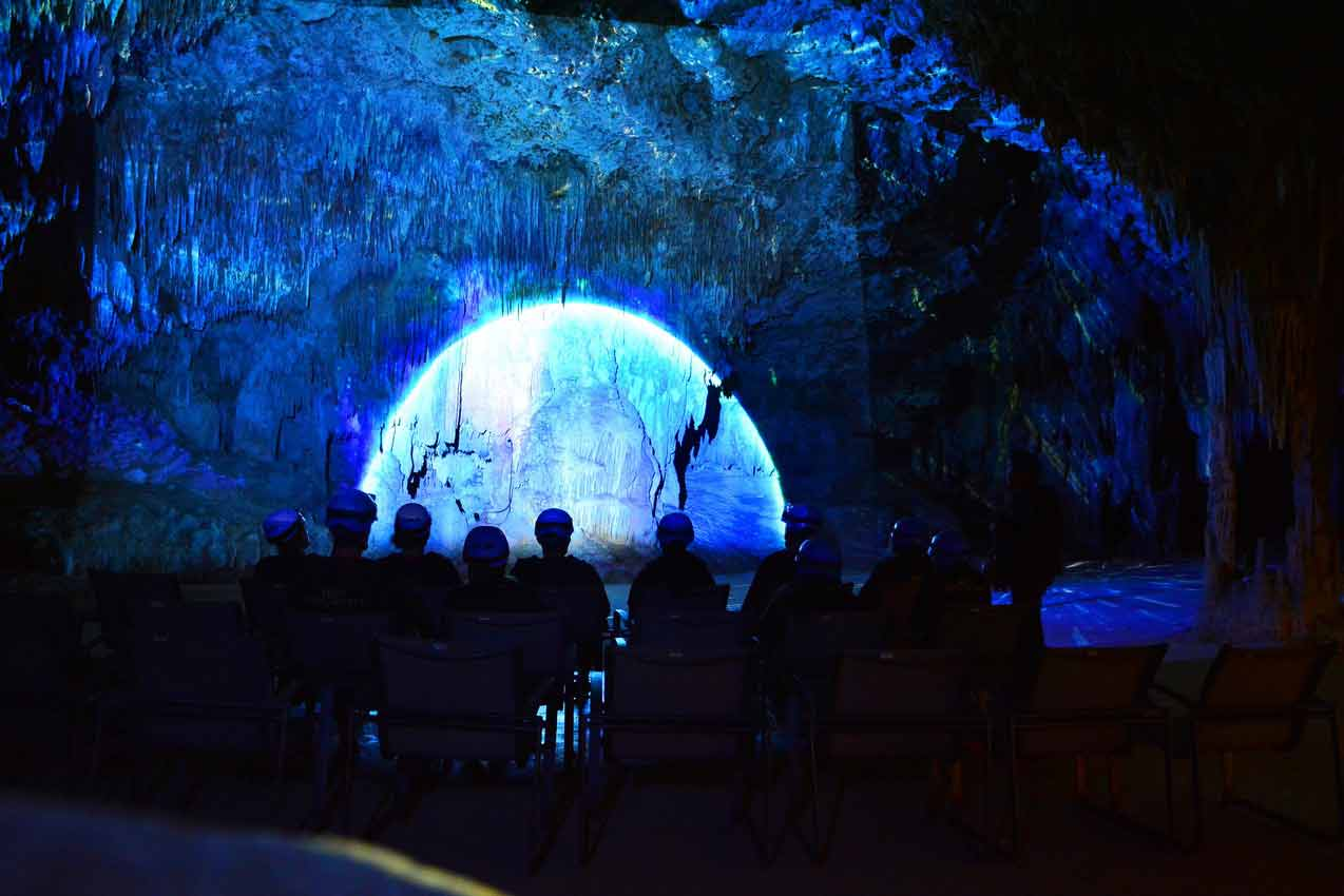 group-of-tourists-watching-light-show-on-rio-secreto-cave-wall