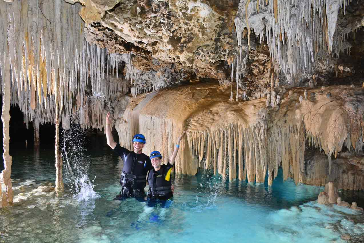 man-and-woman-splashing-water-in-rio-secreto-tour-underground-cenote-pool