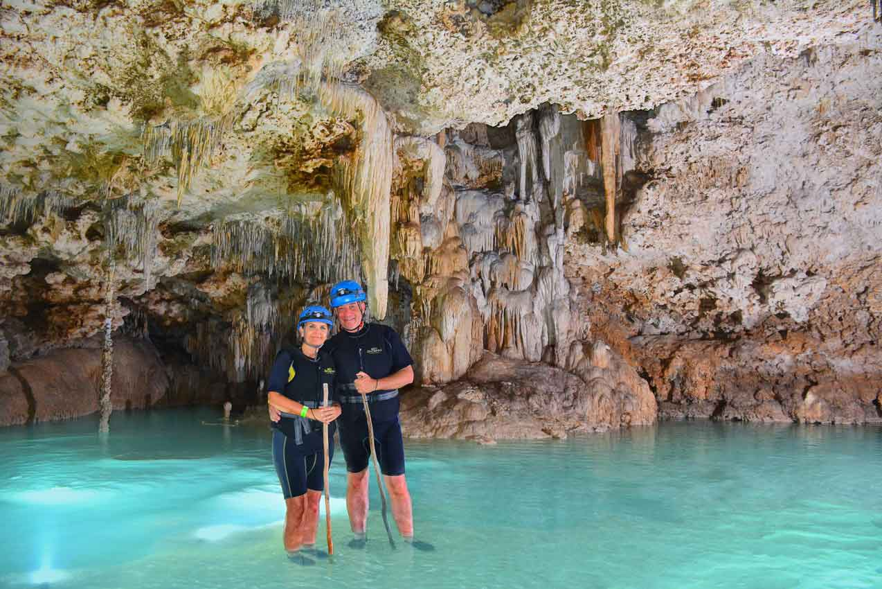 man-and-woman-standing-ankle-deep-in-clear-blue-water-in-cave-during-rio-secreto-guided-activity
