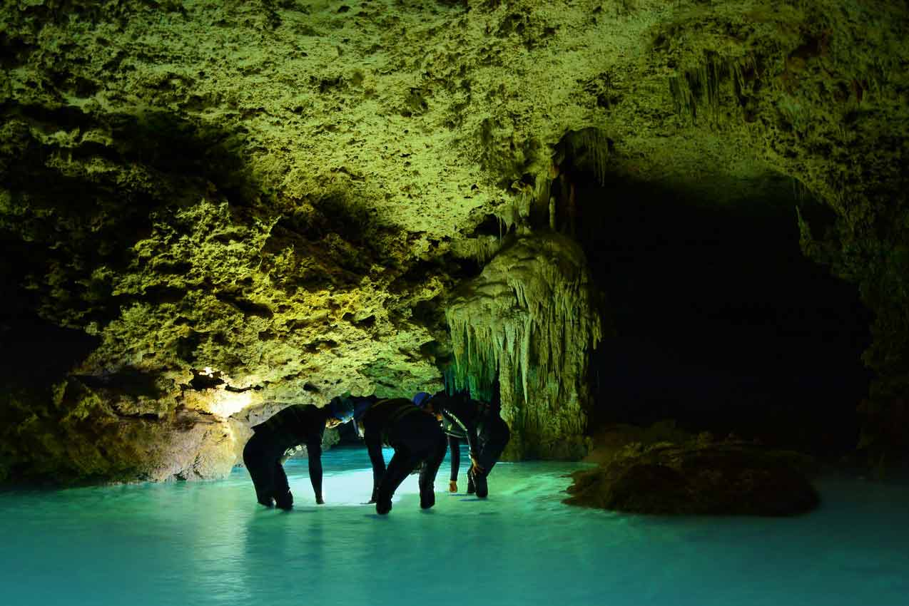 three-tourists-in-dark-rio-secreto-mexcio-cave-during-tour