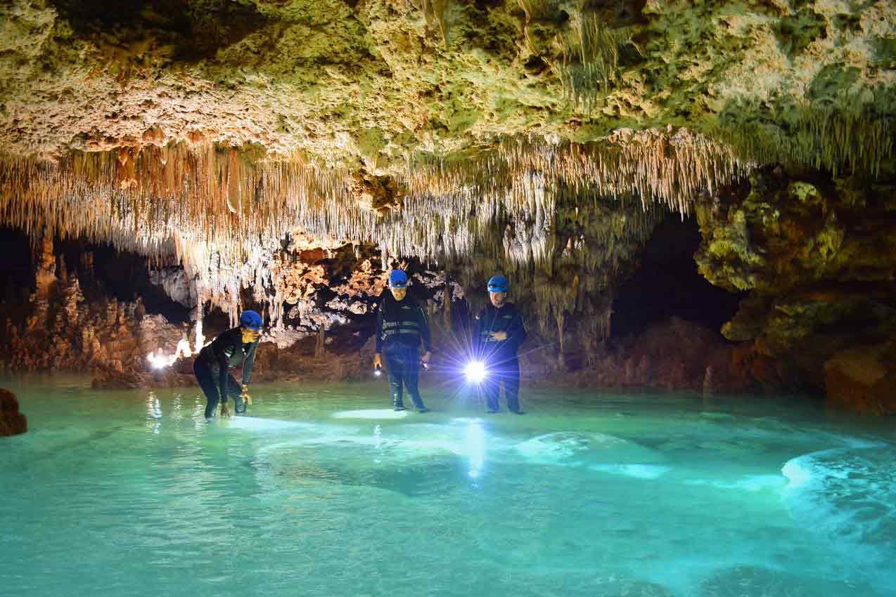 two-tourists-shining-flashlight-into-clear-water-in-rio-secreto-playa-del-carmen-tour-caves