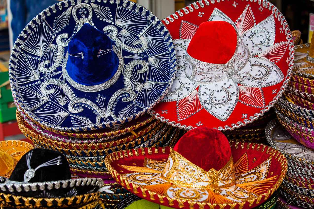 Several stacks of sombreros for sale on the street.