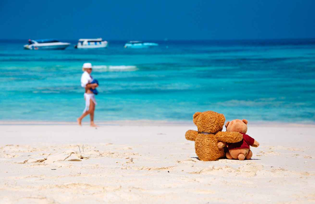Two teddy bears sitting on the beach in Playa Del Carmen.