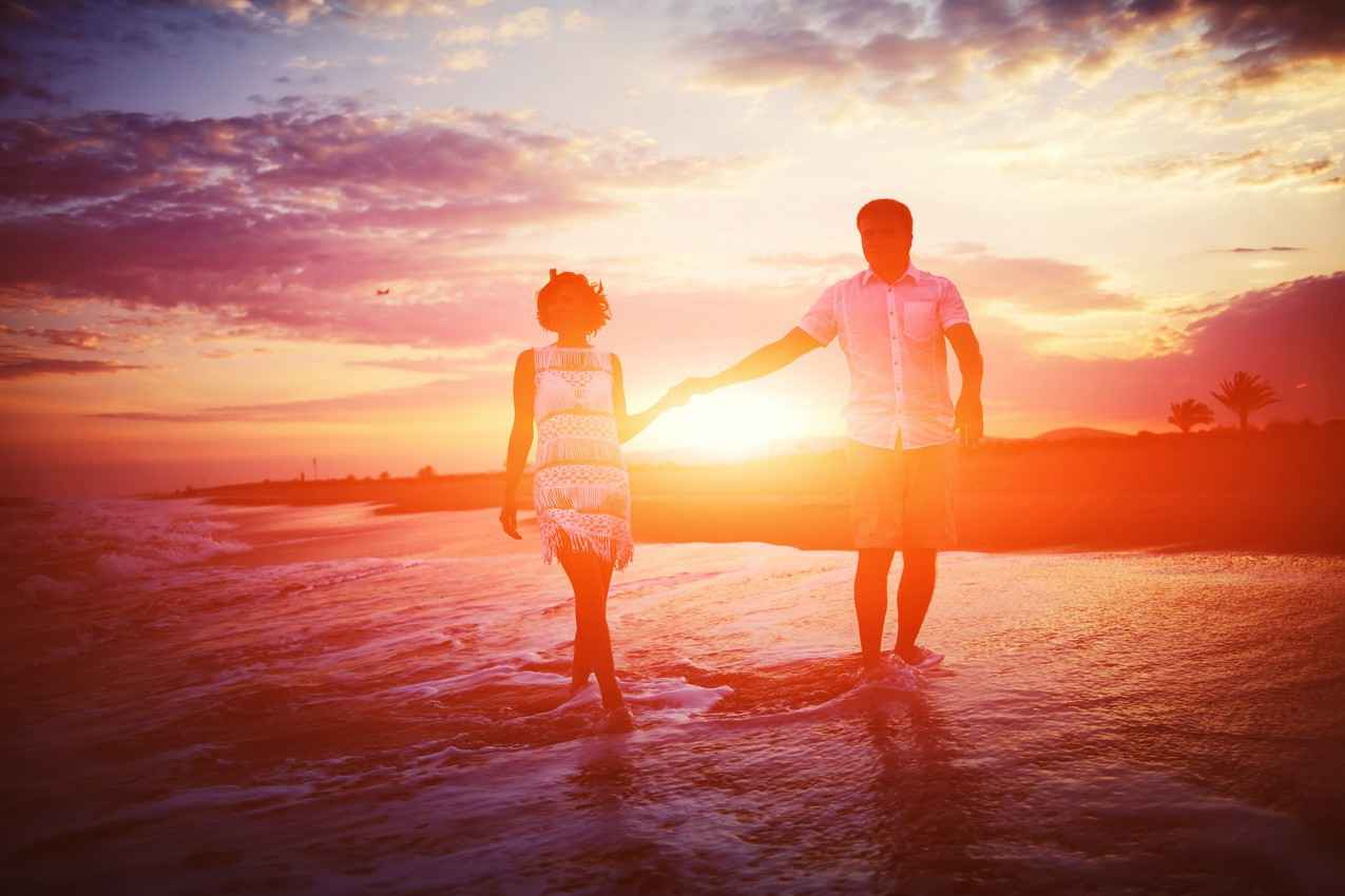A man and a woman walking on the beach at sunset with waves lapping at their feet.