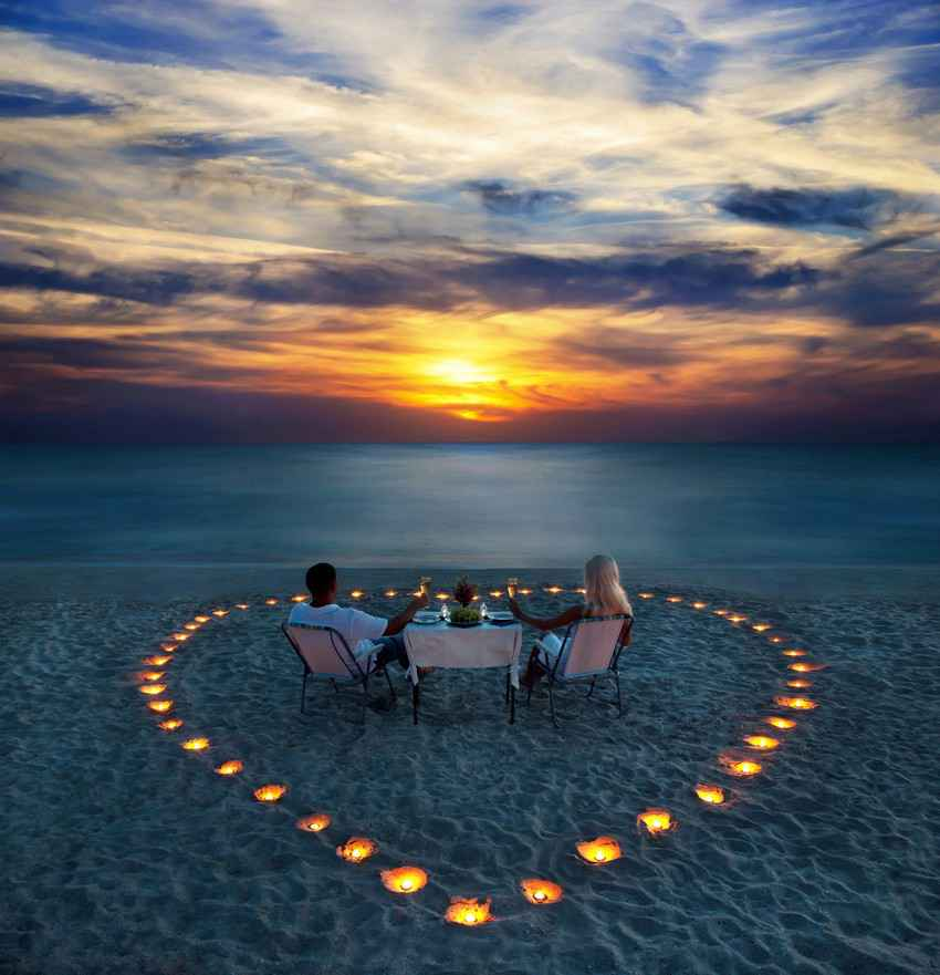 A recently married couple sitting on the beach watching the sunset inside of a large heart that was created with burning candles.