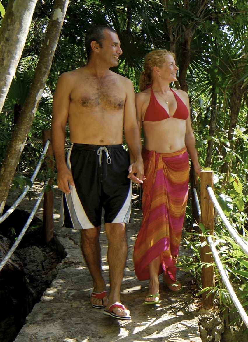 A hot woman in a bikini and a man in swimming shorts taking a romantic walk in the jungle.