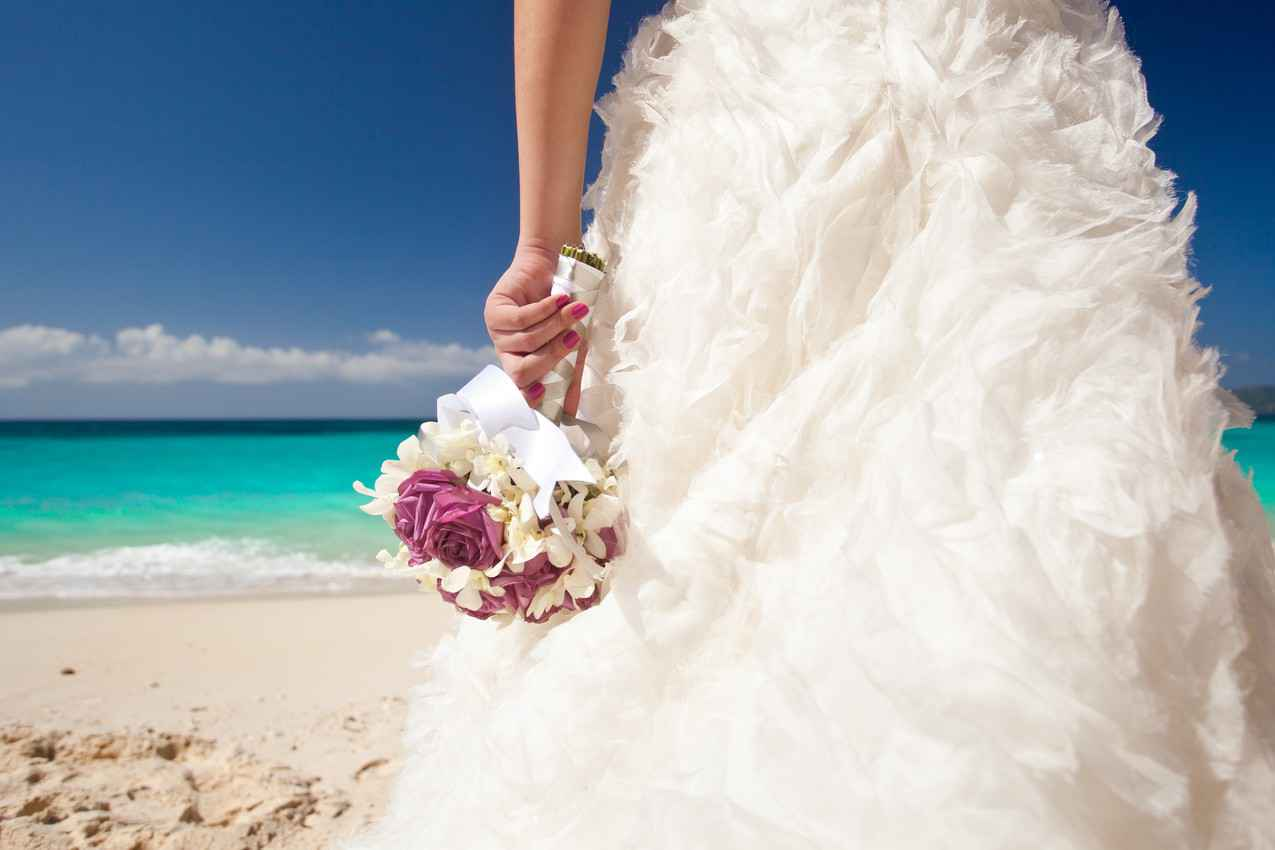 A beautiful wedding dress and bouquet of flowers on the beach in Playa Del Carmen.