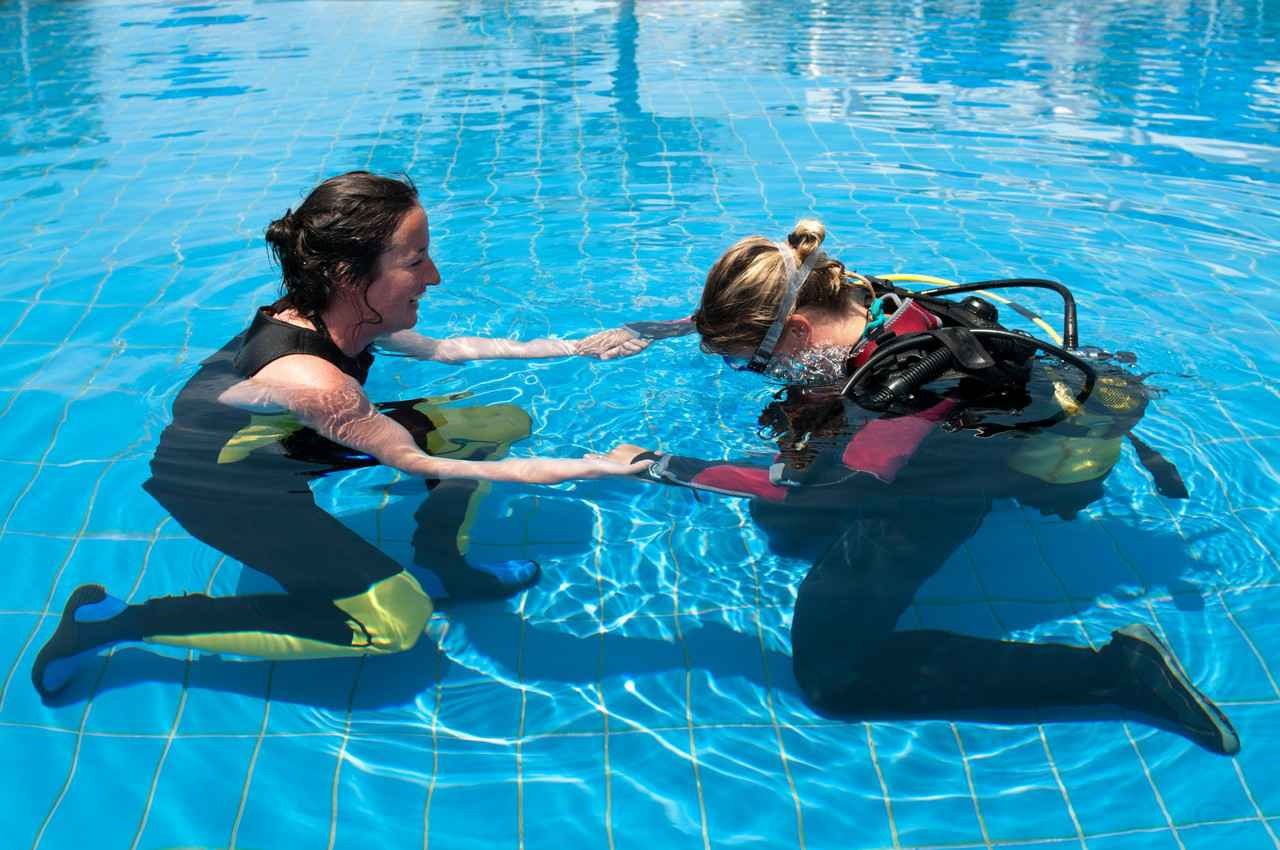 A female scuba diving instructor was working with a female student in a large swimming pool.