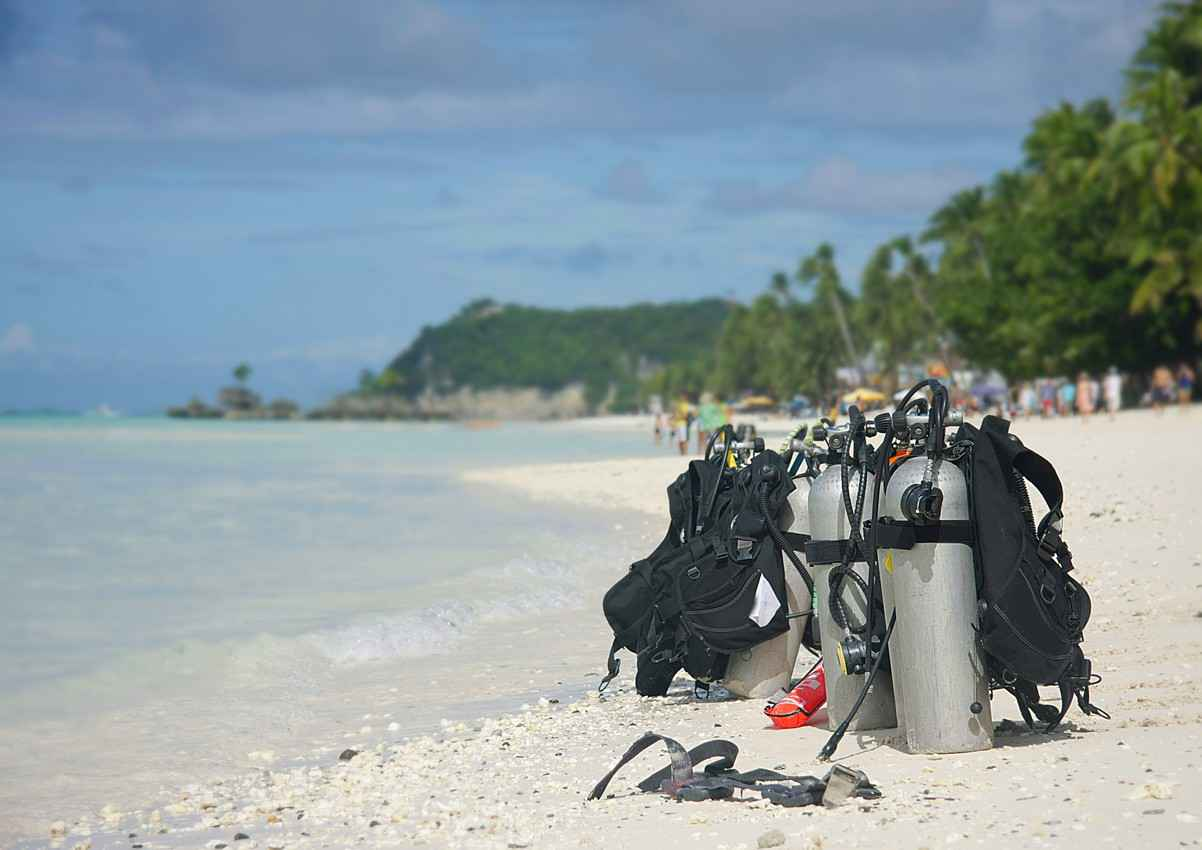 Several scuba diving tanks and an array of equipment on a beach near the Tulum ruins.