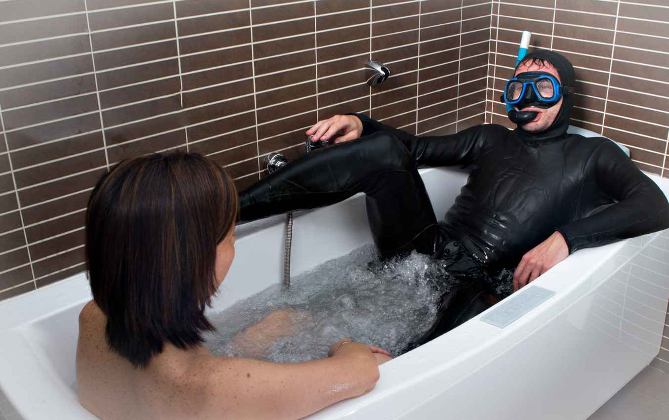 A funny scuba diver who is diving with his wife in his bathtub.