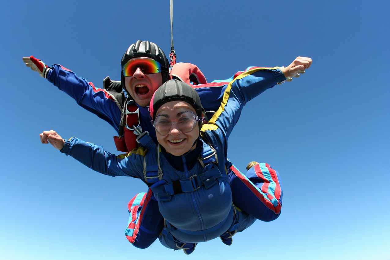 A woman and a skydiving instructor doing a tandem jump.