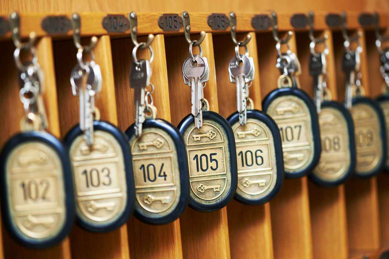 A group of numbered room keys hanging from a desk at a reception area.