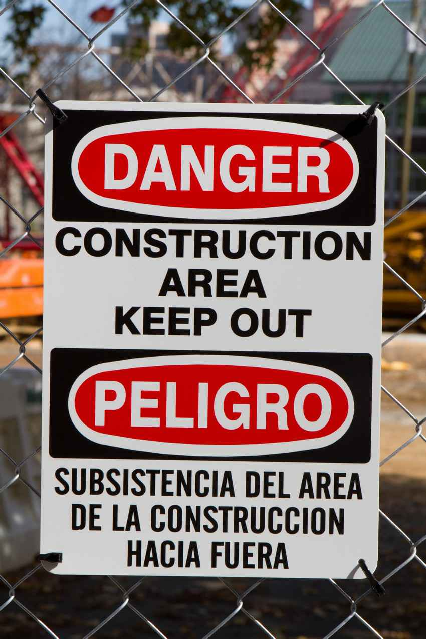 A CONSTRUCTION AREA KEEP OUT sign in both English and Spanish.