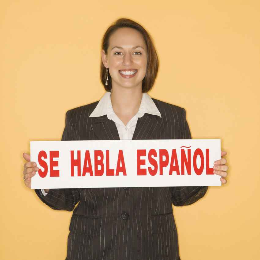 A Spanish teacher holding a sign that says, SE HABLA ESPANOL.