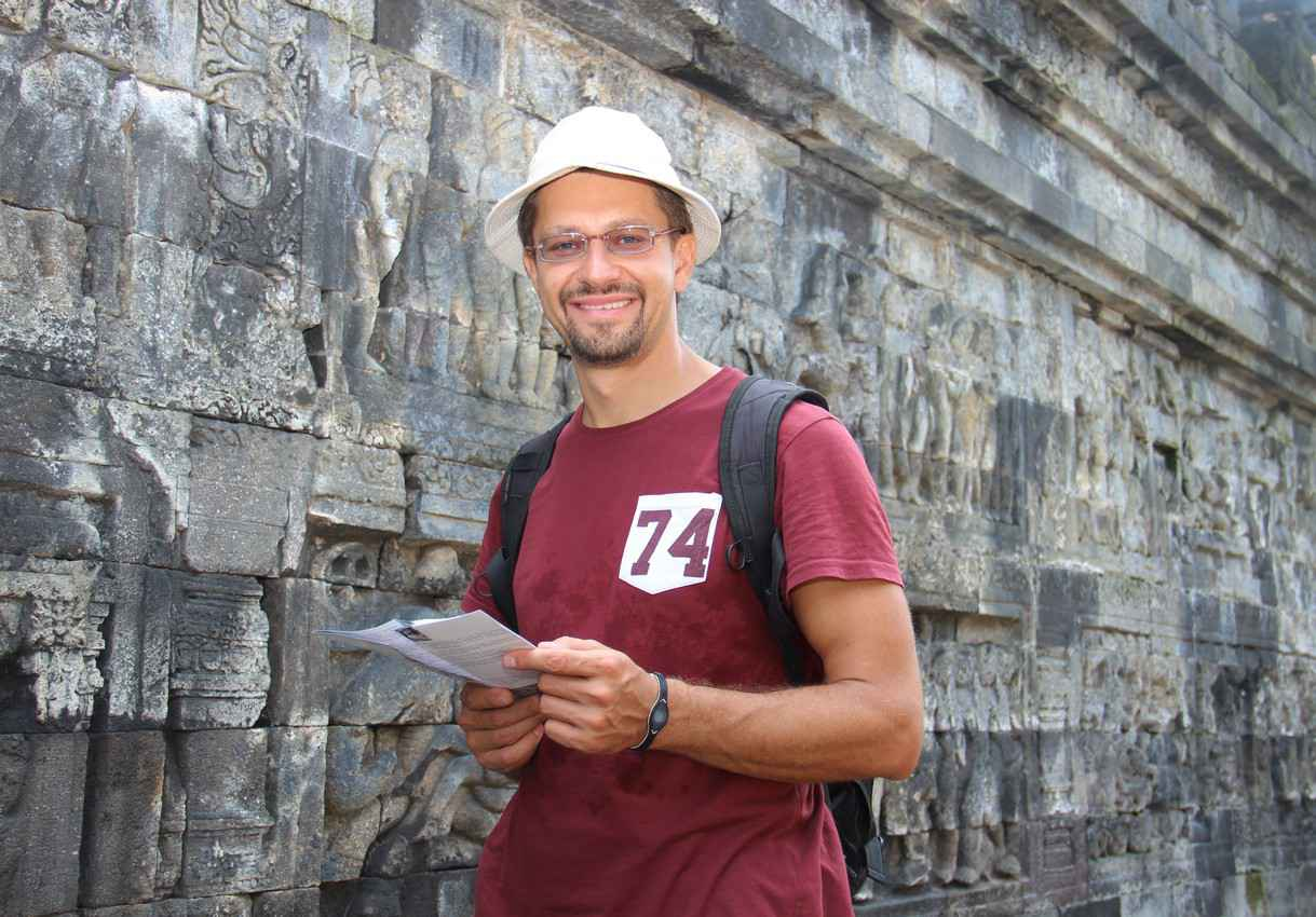 A student with a backpack looking at a tour map next to some Mayan ruins.