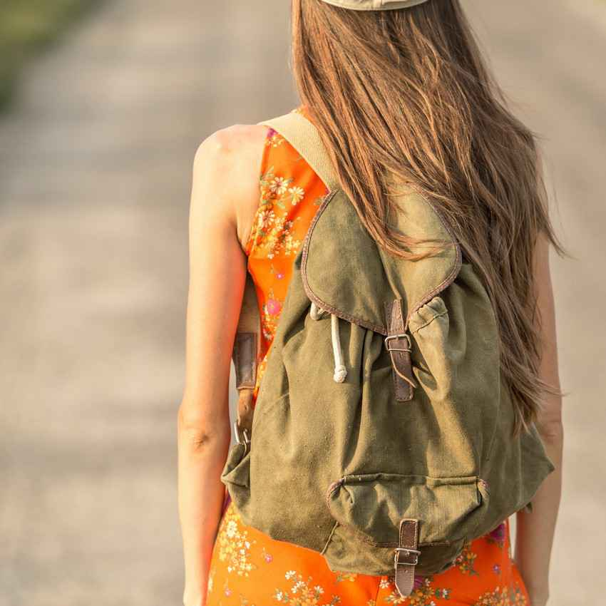 A young woman with a backpack walking down the street in Playa Del Carmen.