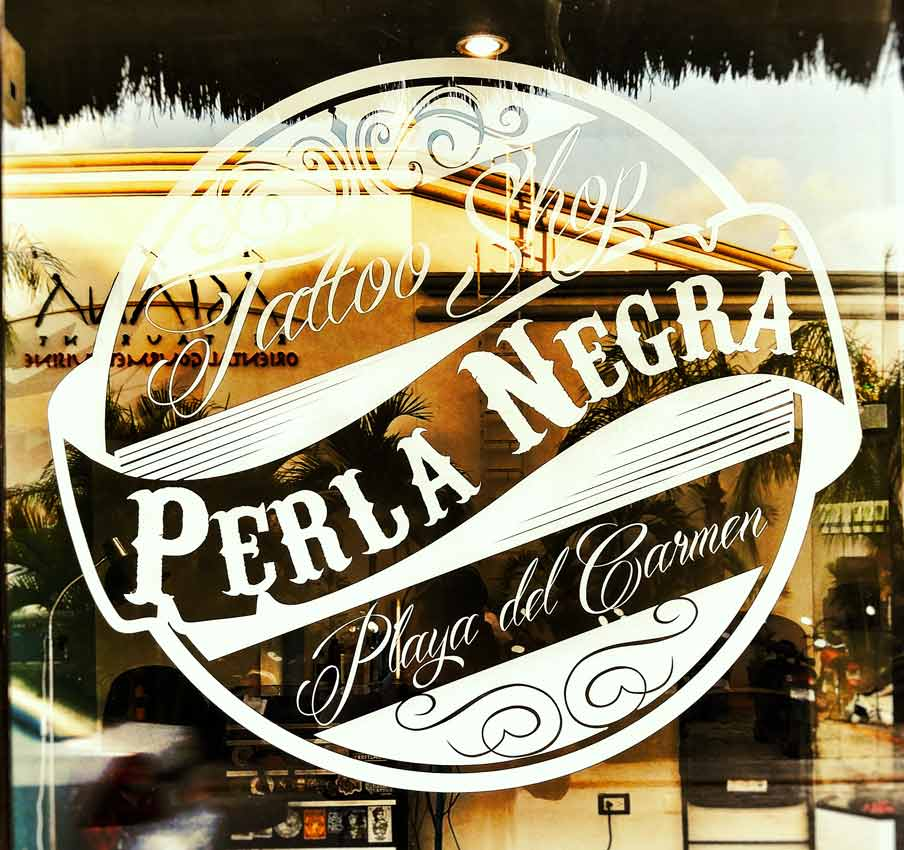 The Perla Negra sign and logo on a window in Playa Del Carmen.