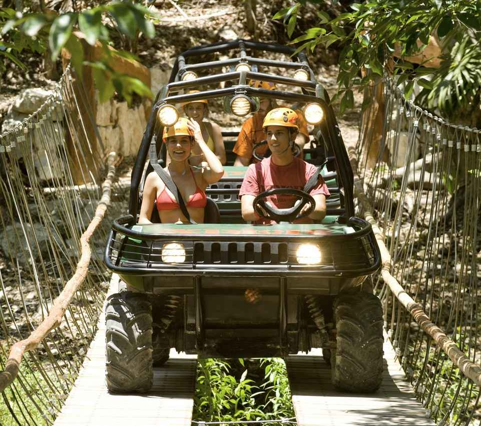 A group of people riding in an ATV at the Xplor themepark.