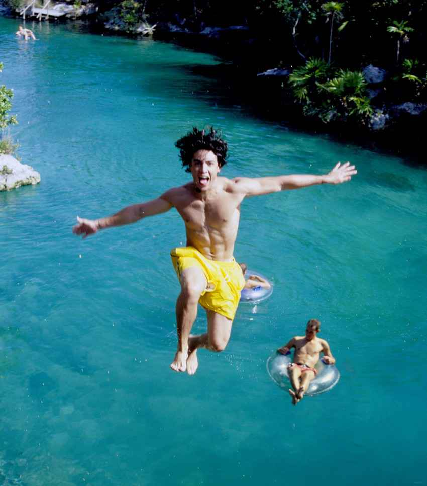 A man jumping off of a cliff into a cenote at Xel-Ha themepark.