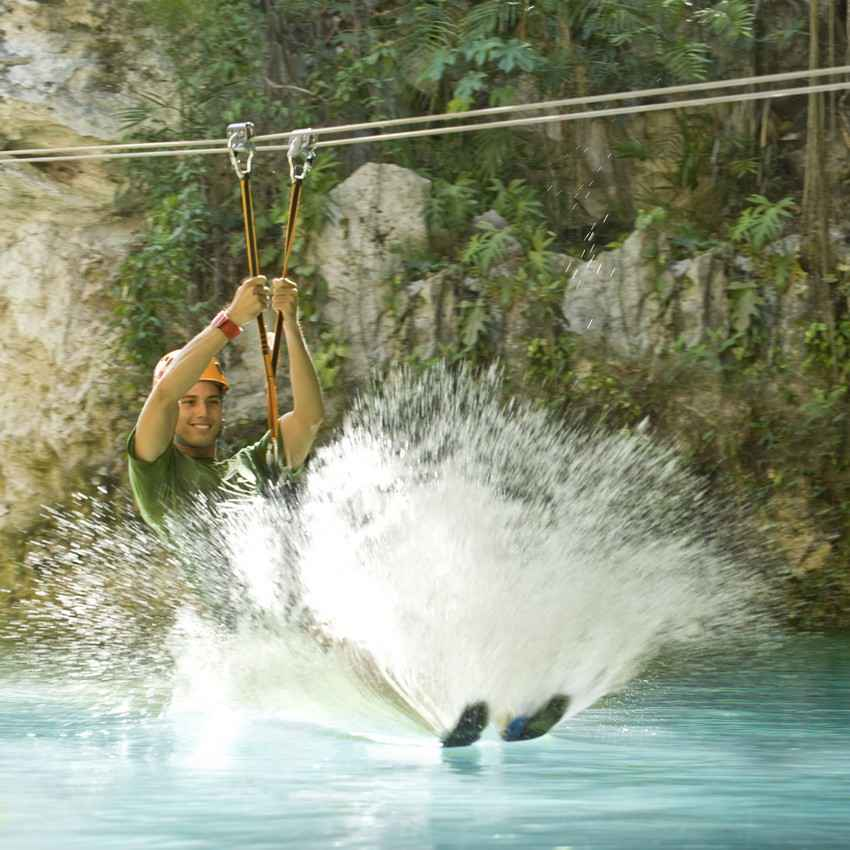 A man riding a zip line into a cenote in the Riviera Maya.