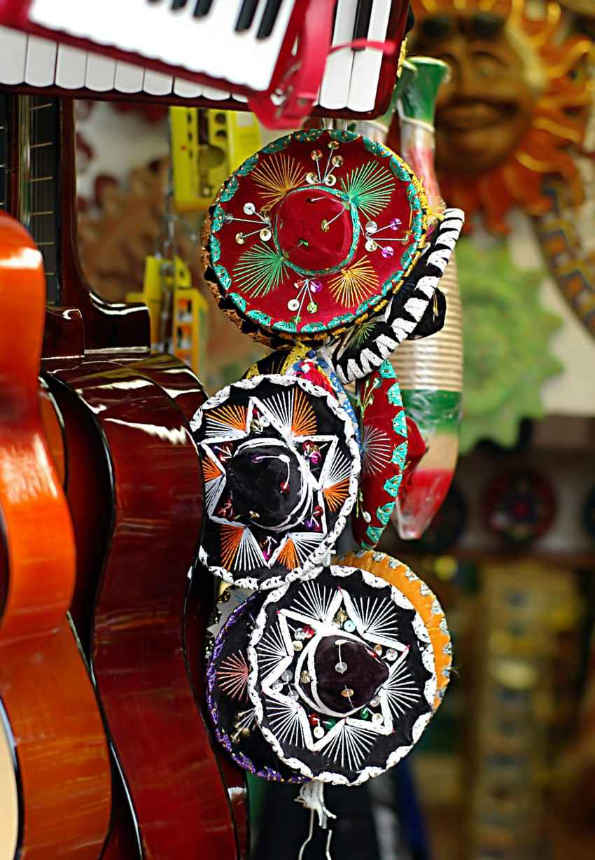 A stack of sombreros and several guitars for sale on a Playa Del Carmen street.