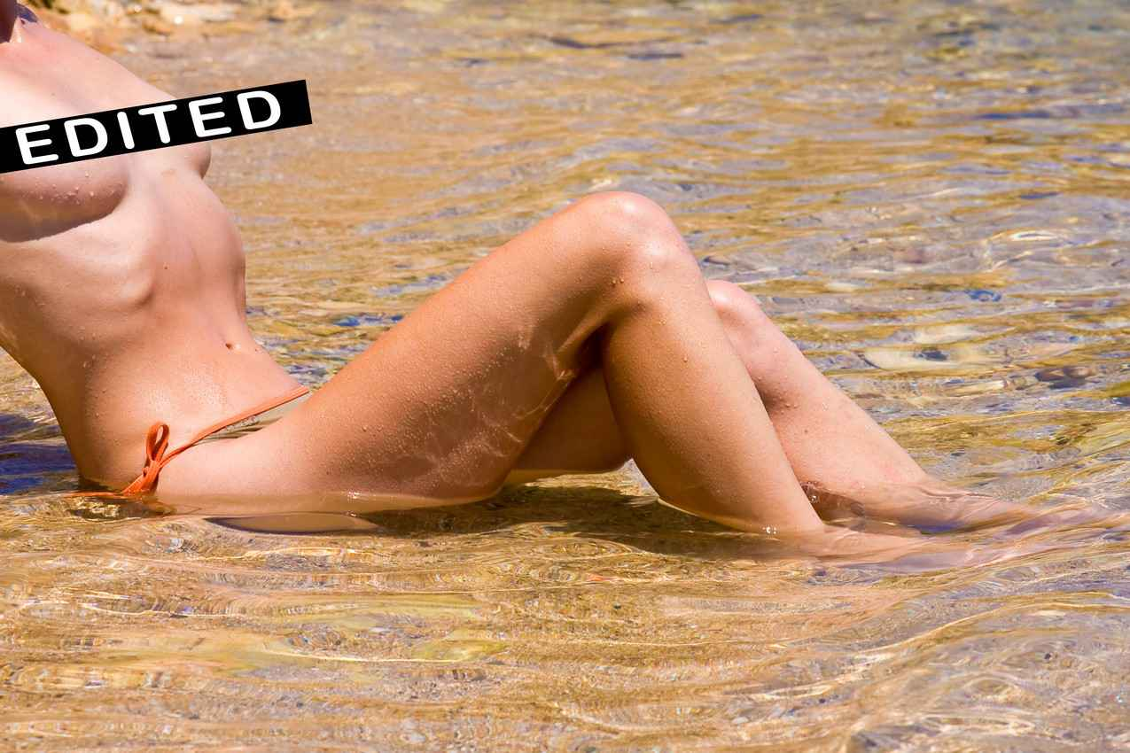 A topless woman sitting in shallow water at a beach.