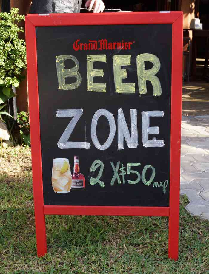 "A ""BEER ZONE"" sign showing a ""Two beers for 50 pesos"" special."