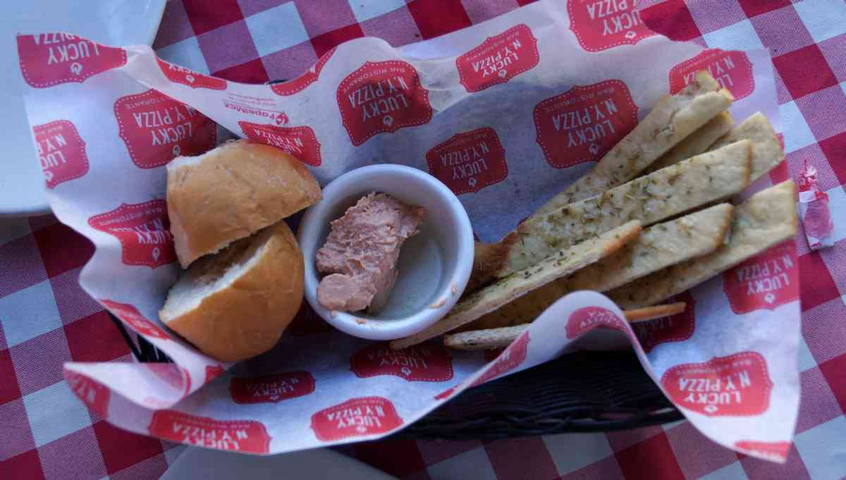 A basket of delicious breadsticks with amazing dip at Lucky Luciano pizza restaurant.