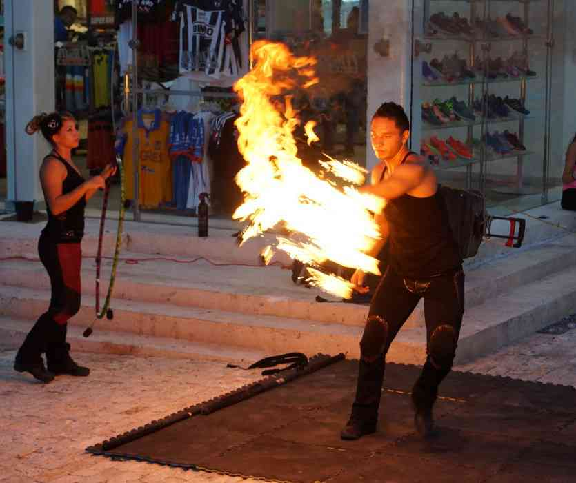 Male and female fire dancers swinging fire sticks around their bodies.