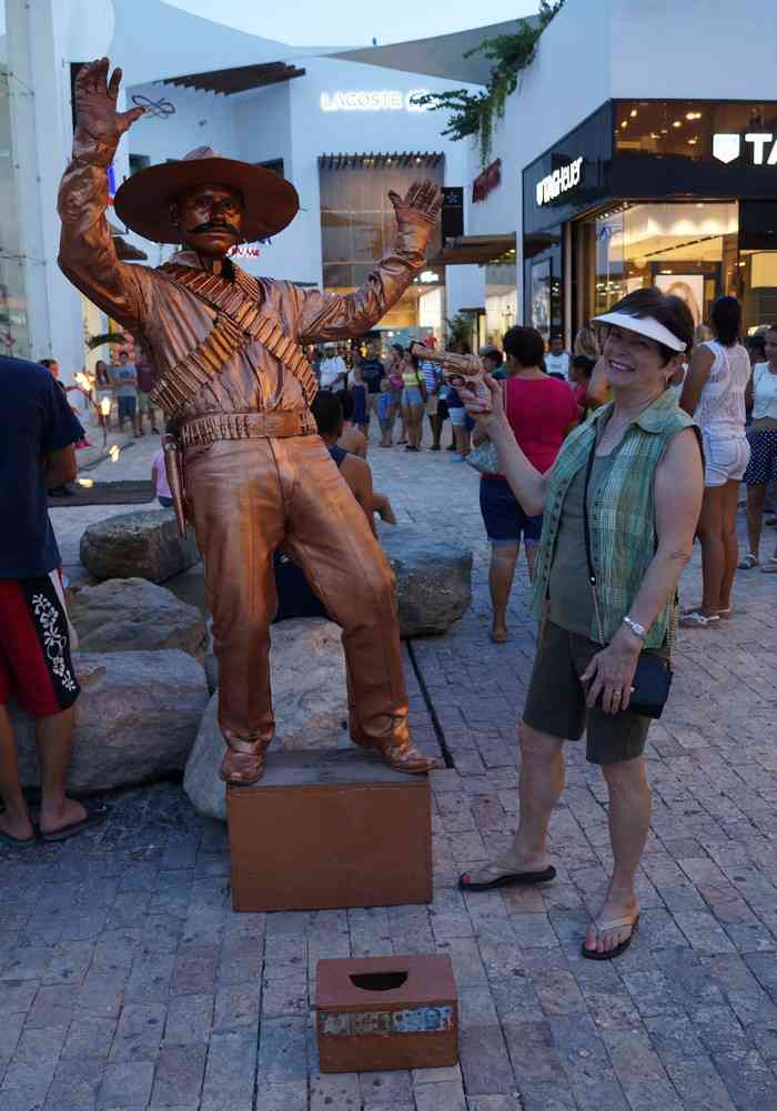 My mom smiling while stealing a gun and holding up the statue man on Fifth Avenue in Playa Del Carmen.