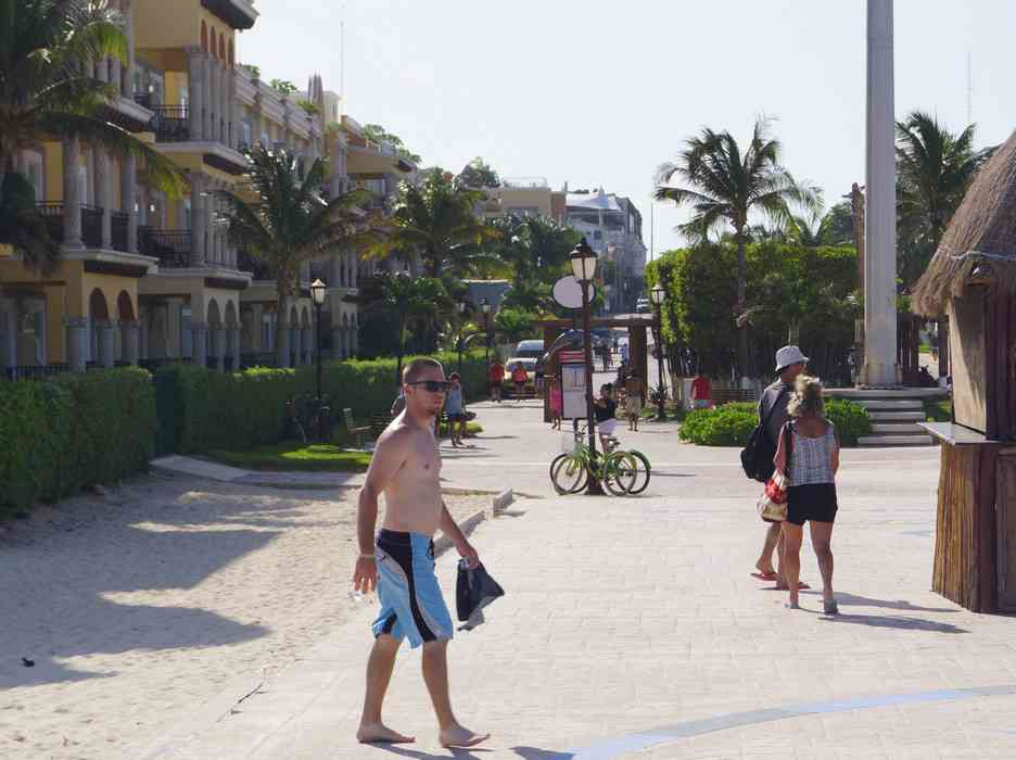 A view of several people walking near the beach and condos.