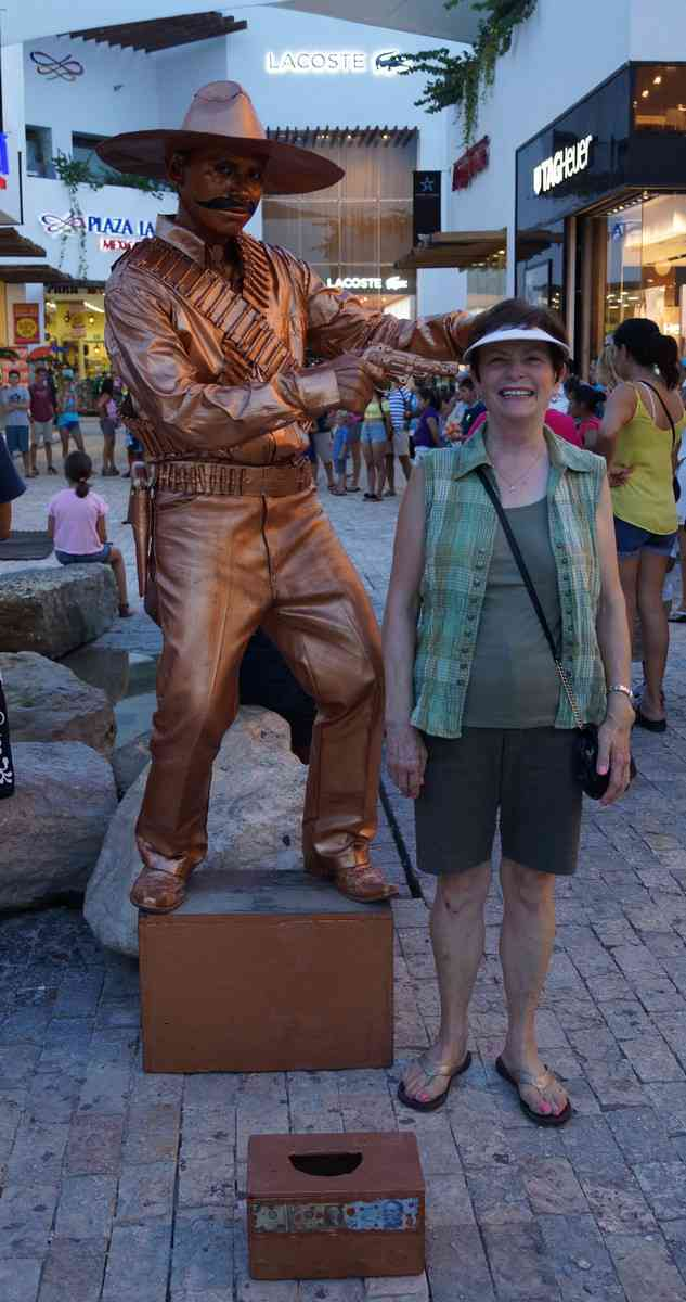 A statue man holding a gun to my mom's head on Fifth Avenue in Playa Del Carmen.
