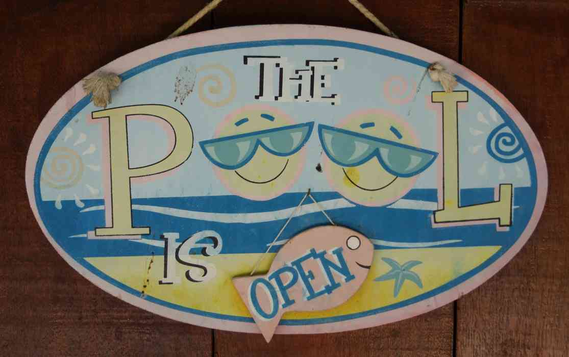 "A sign that reads ""The Pool Is Open."""