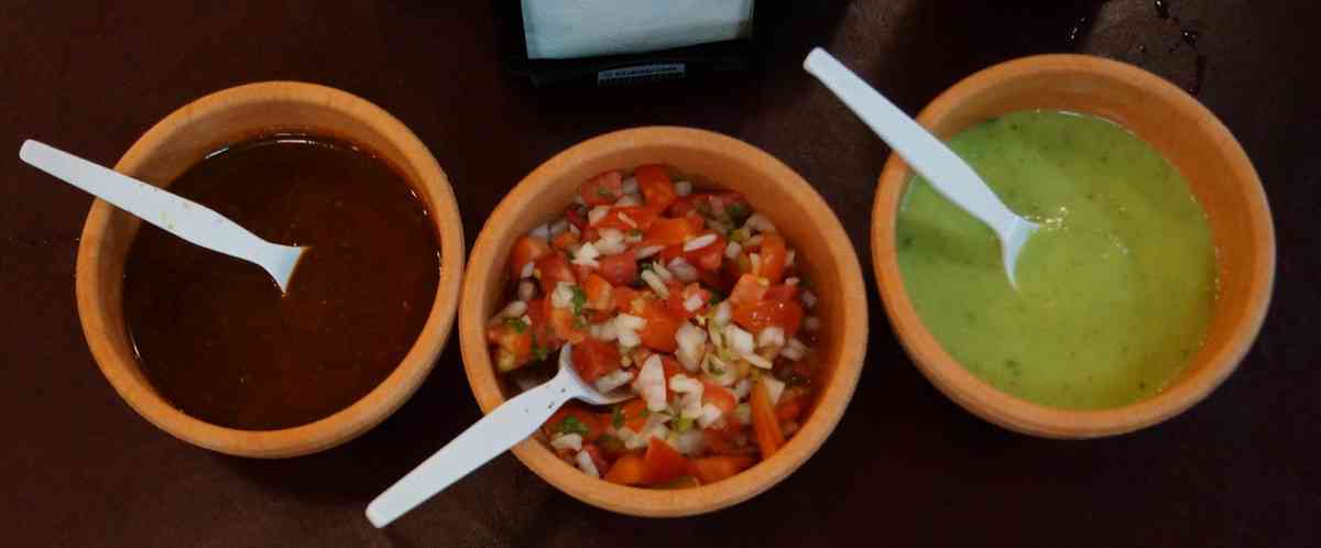 Three different flavored salsas in separate bowls at El Fogon restaurant in Playa Del Carmen.