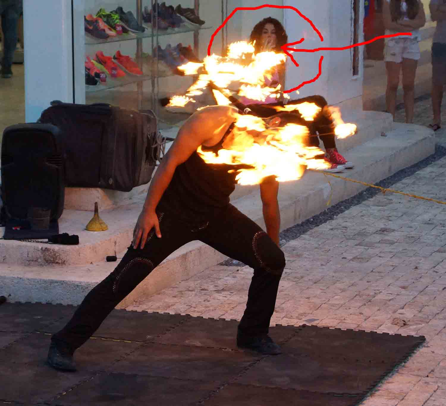 A woman lighting her cigarette on a fire dancer's burning pole.