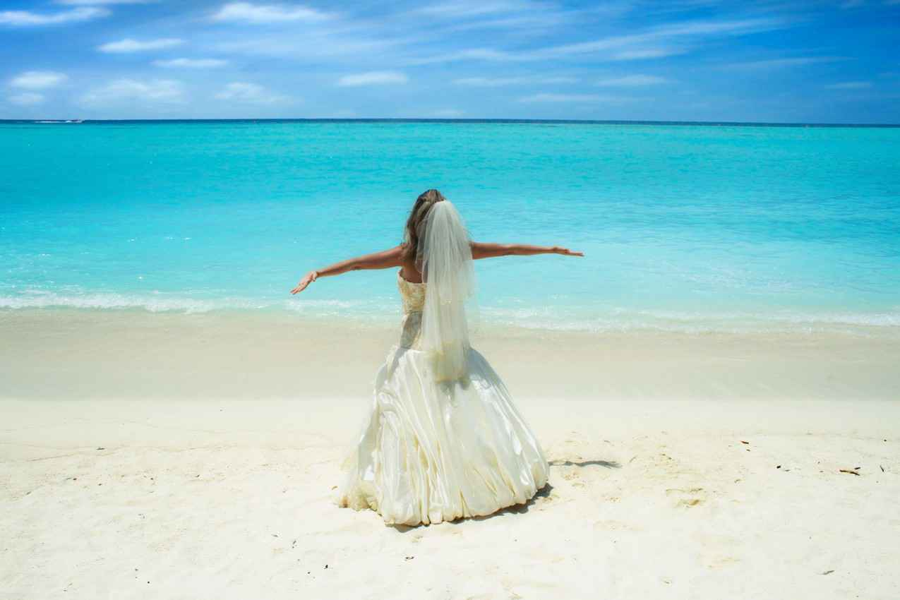A bride standing on a beach with her arms outstretched.