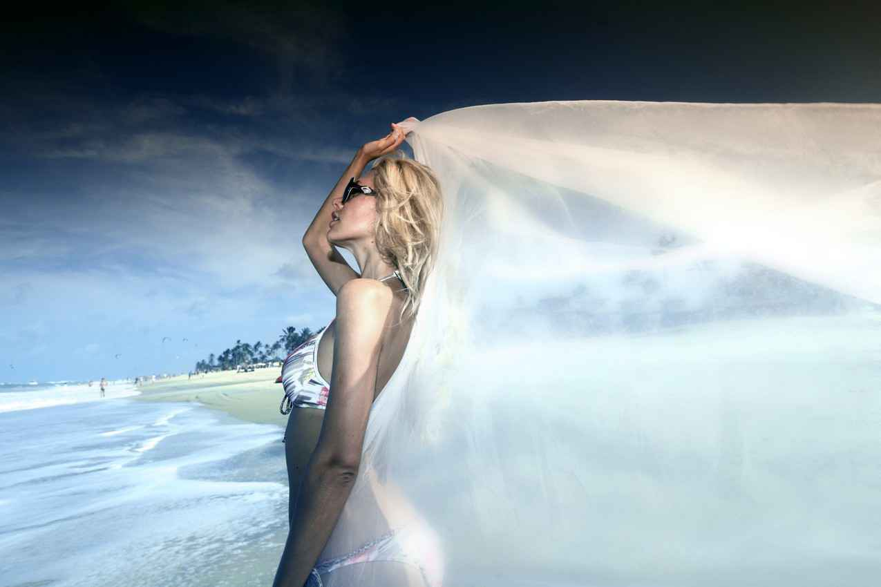 A photograph of a woman on the beach holding her wedding veil which is blowing in the wind.