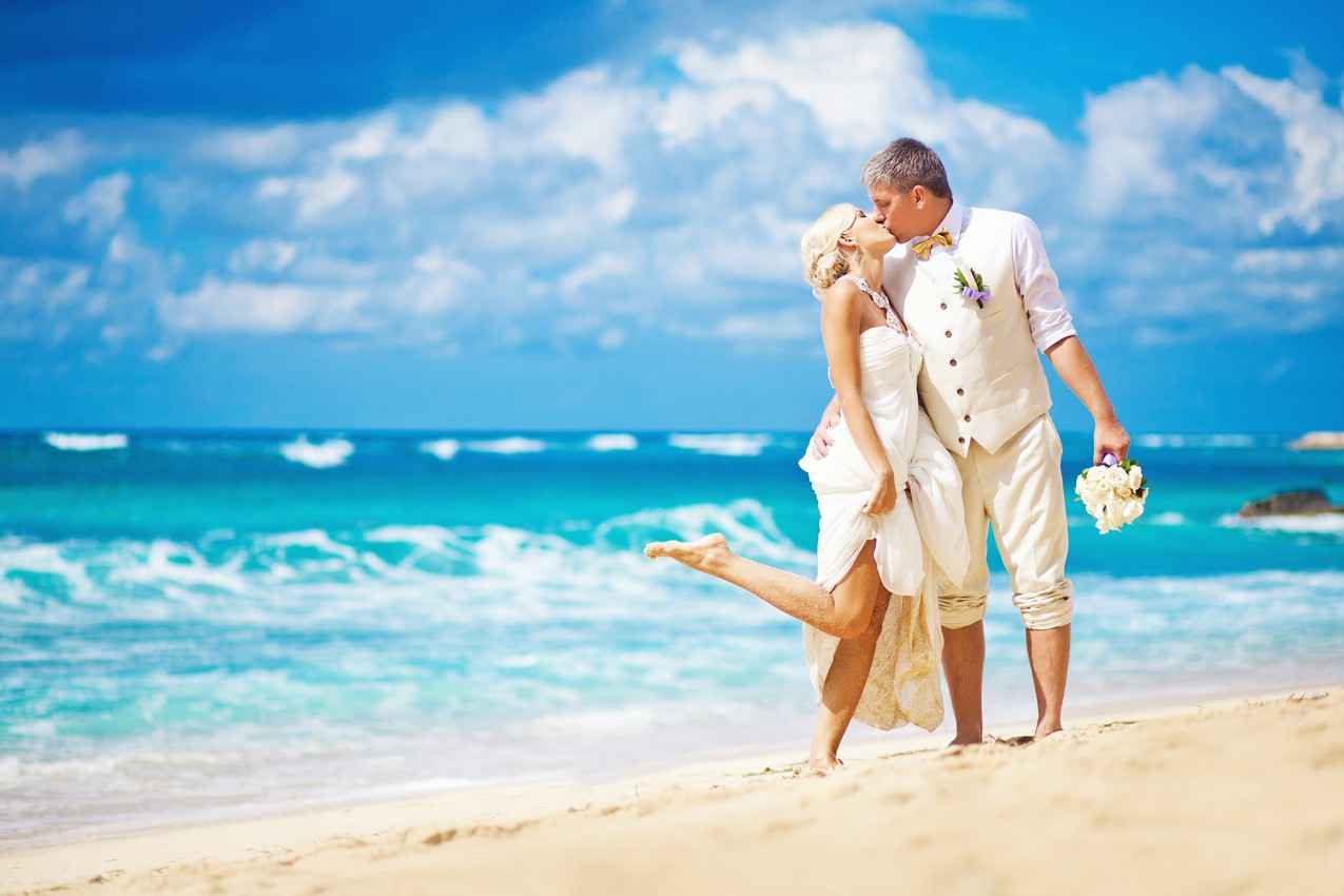 A recently married couple kissing on the beach with the man holding a flower bouquet and the leg of the woman upright in the air.