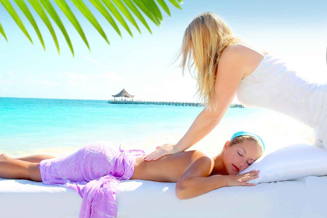 One sexy woman giving another sexy woman a massage on the beach.