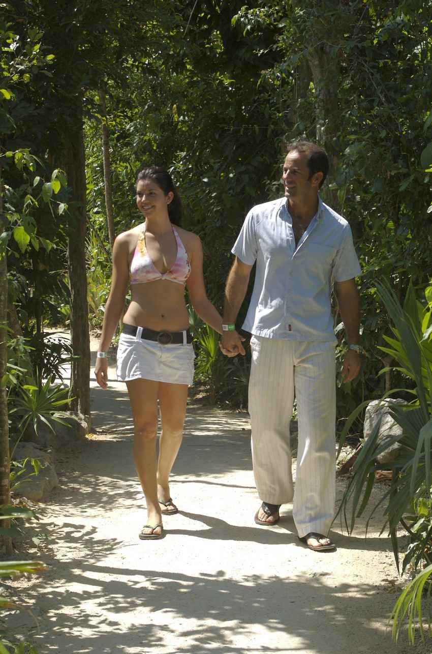 A super hot woman with huge boobs walking hand-in-hand with a man during a jungle tour.