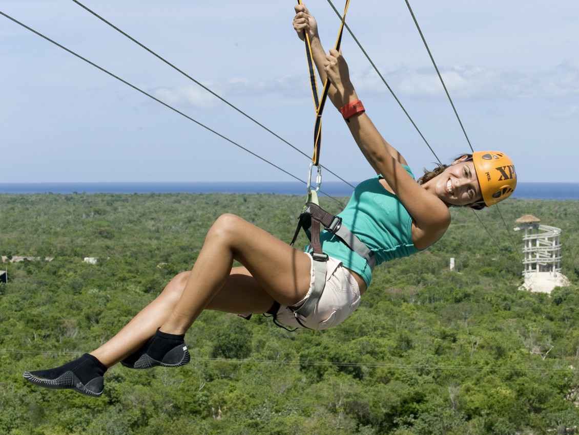 A woman hanging from a zip line at Xplor themepark.