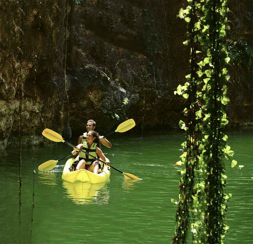 Several tourists riding a kayak near a cenote.