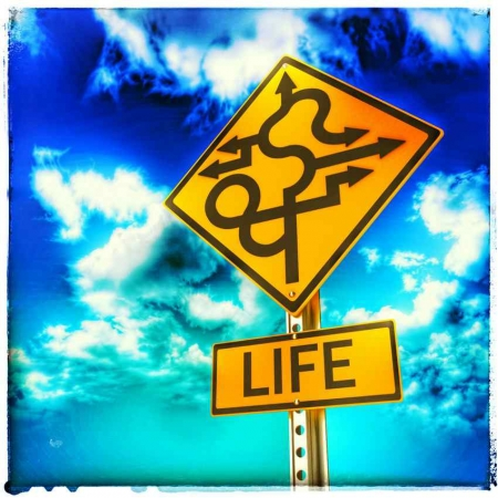 "A sign with arrows pointing in many directions and ""LIFE"" written underneath."