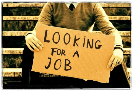"A man holding a sign that says ""LOOKING FOR A JOB."""