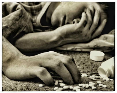 A black and white picture of a man lying on the floor with sleeping pills next to him.