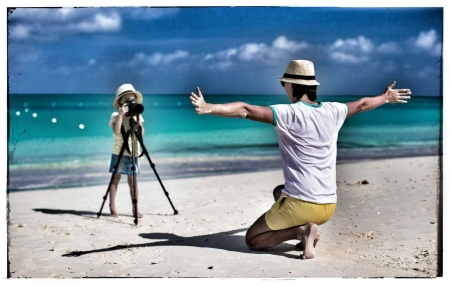 A young woman taking a photograph of a man at the beach.