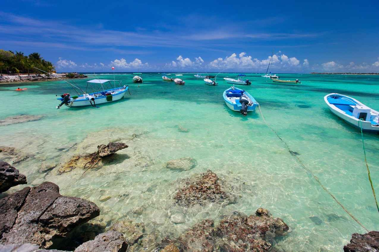 Several boats docked in the water near the Akumal shorel