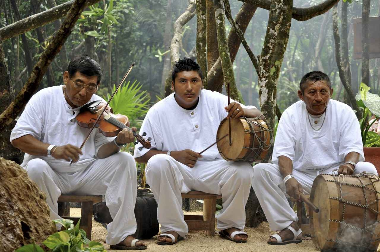 Three men playing Mayan music in the jungle.