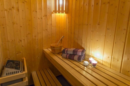 A wooden sauna with towels and massage tools.